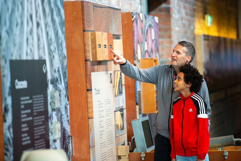 A parent and a child looking at an exhibit about timber