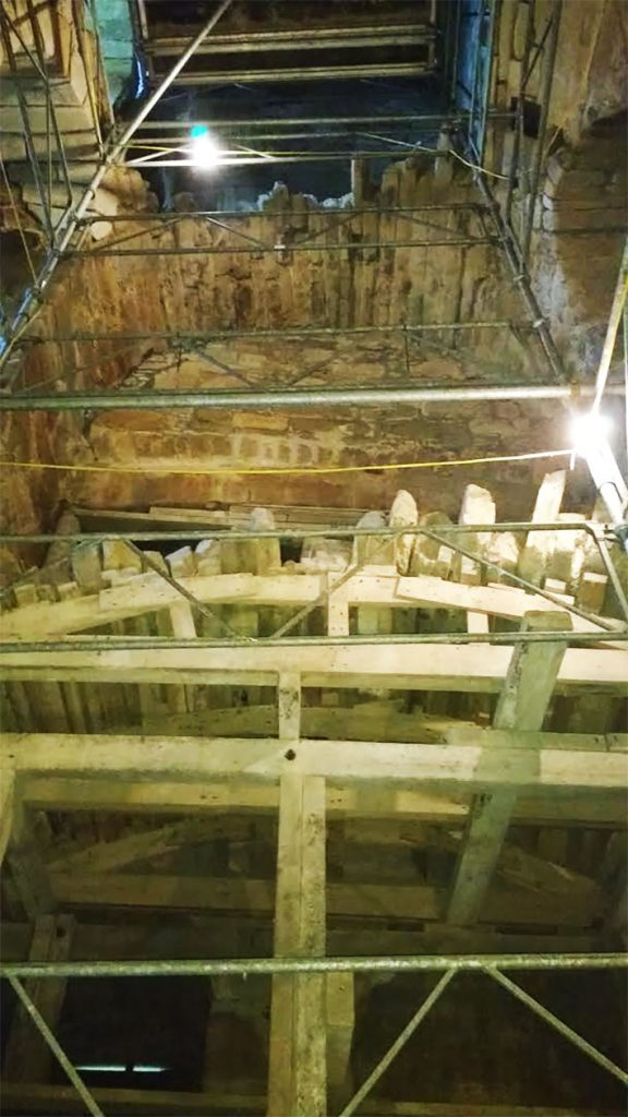 A picture from the perspective of someone stood at the bottom of a building's (Clackmannan Tower's) interior, showing supporting scafffolding and lit by bright lights.