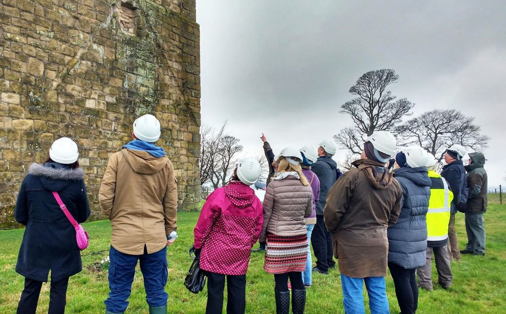 A group of about ten people, dressed in outdoor clothing and hard hats, stand on grass outside an old stone building (Clackmannan Tower), looking up.