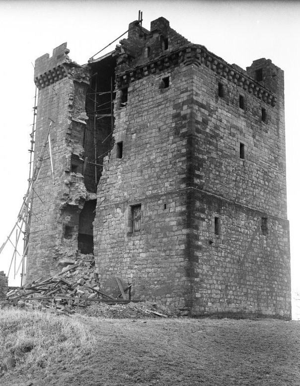A black and white photo of a medieval tower (Clackmannan Tower) with a large area of collapsed stone in one wall.