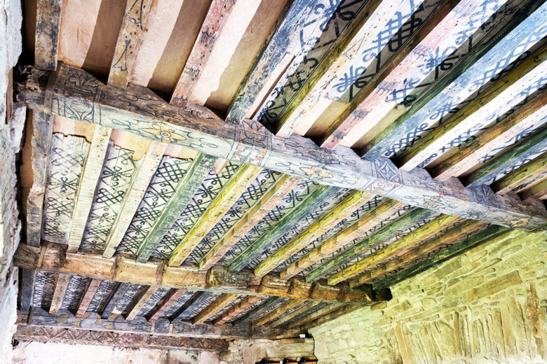 Wooden ceiling beams with black patterned markings on them