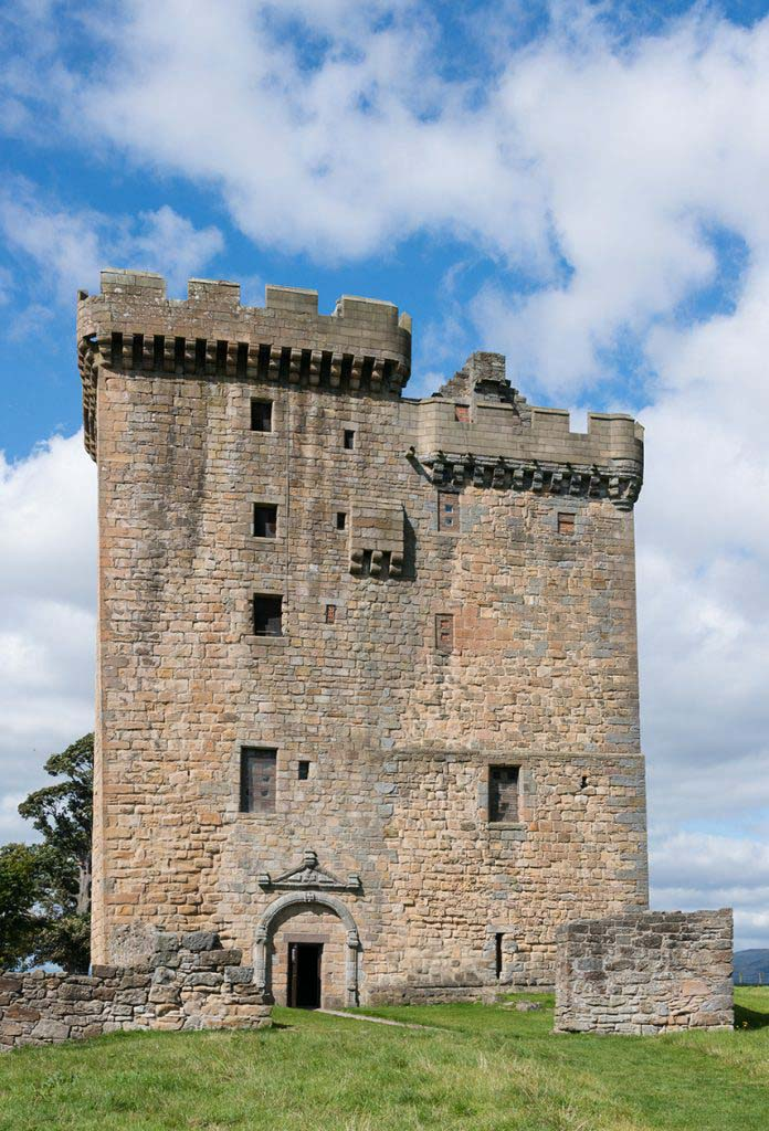 A medieval tower (Clackmannan Tower) sat set in green grassy surroundings, photographed against a blue sky with white, fluffy clouds.