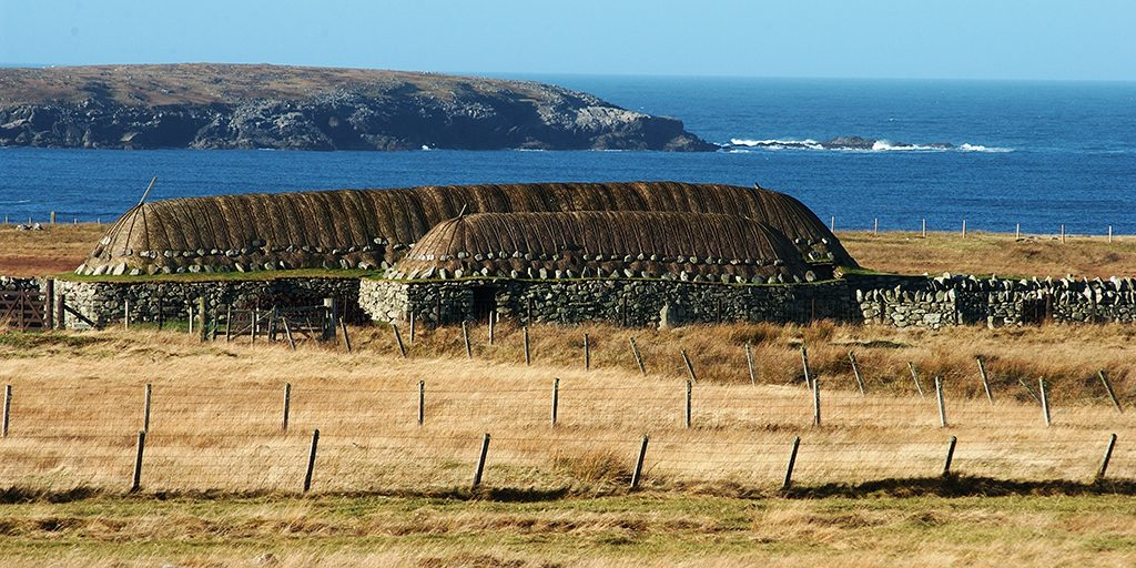 Two low thatched buildings are shown against a backdrop of cliffs, sea and a blue sky.