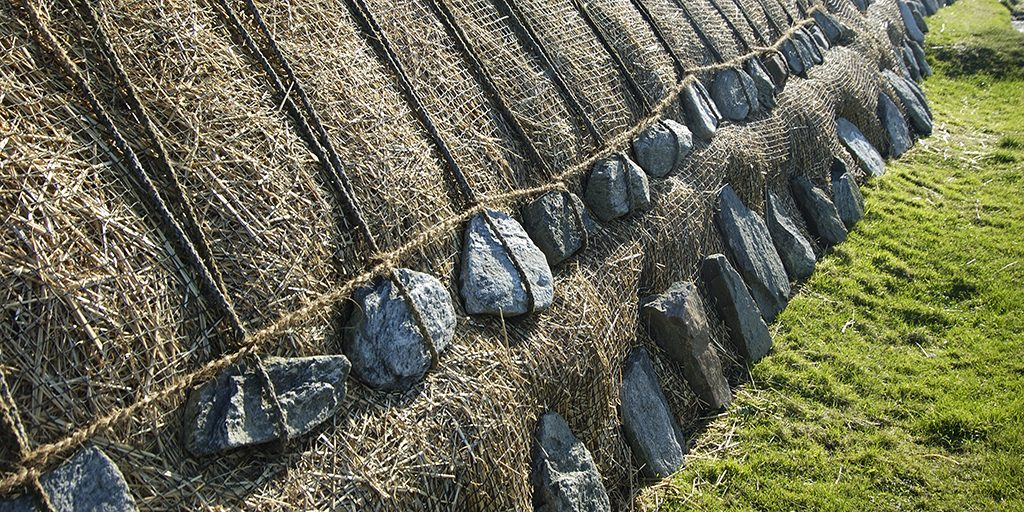 the bottom of a thatched roof resting on a grassy surface, weighted down with stones on pieces of rope.