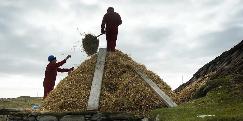 Two people are shown, one standing on top of a pile of straw, passing straw down to the other person using a pitchfork.