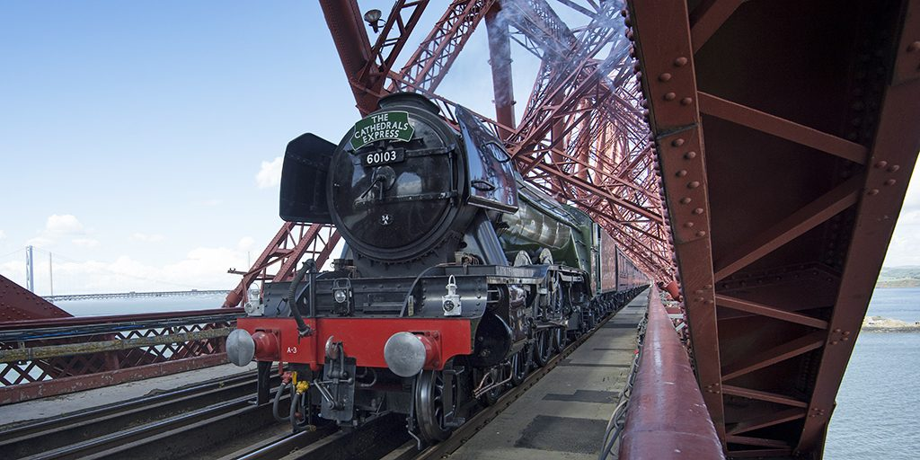 The Flying Scotsman, a steam train, crosses an iron railway bridge, painted red.