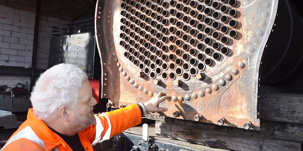 A white haired man points out a feature on a piece of rusty iron associated with steam engines.