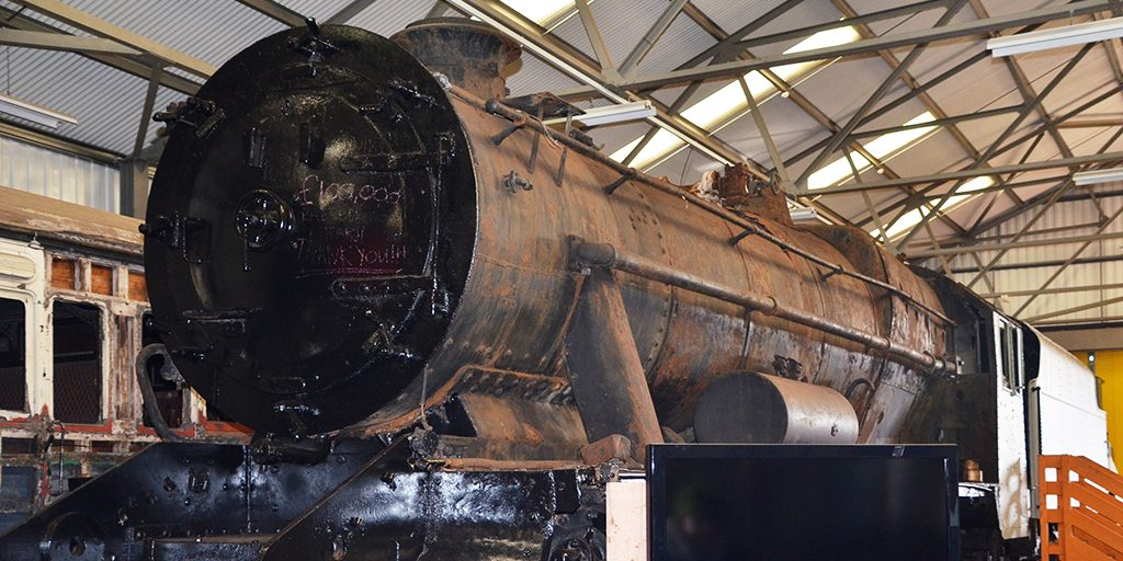 A black painted steam engine in an industrial shed at the Scottish Railway Preservation Society, Bo'ness.