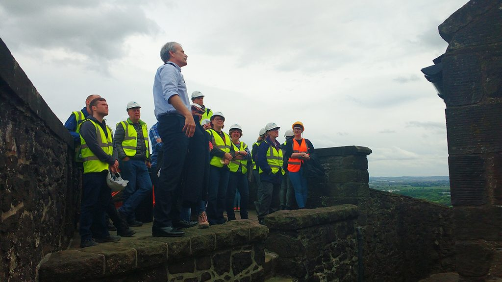 A group of people dressed in safety gear standing on top of a high wall looking out over the view at Stirling Castle