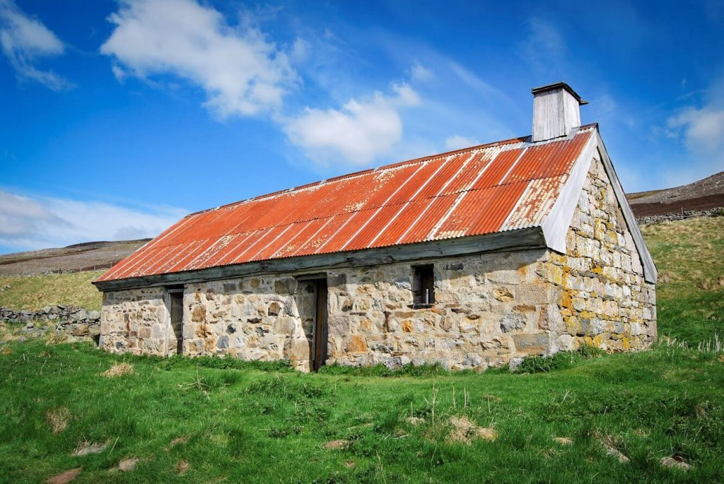 A cottage in the countryside with a corrugated iron roof