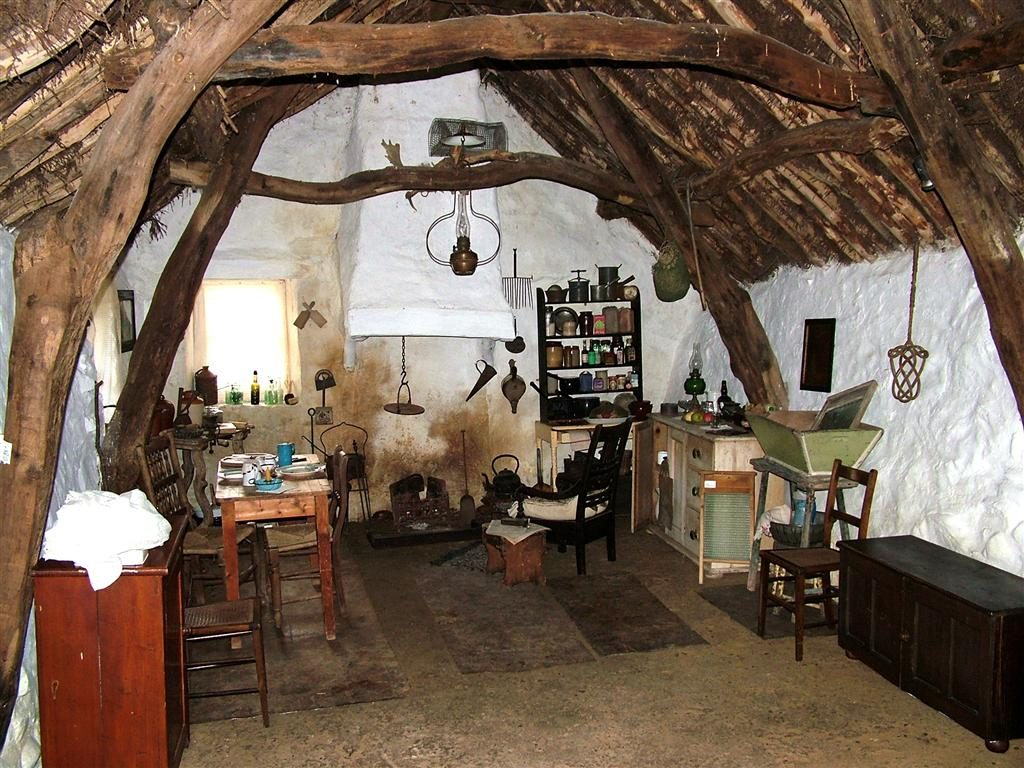 The inside of The Cruck Cottage showing a gable fire, clay walls and furniture