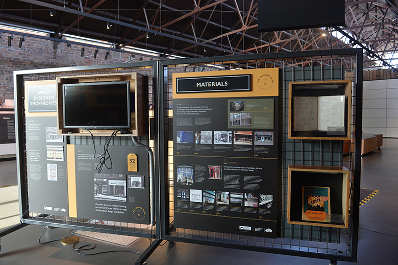 A black and yellow exhibition panel, with photos, wording and a screen on it