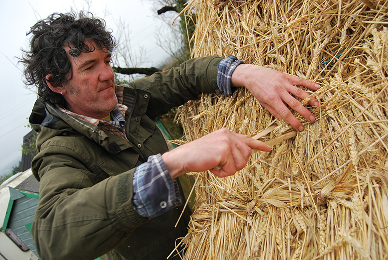 A thatcher demonstrates how to thatch a roof using hazel scobs