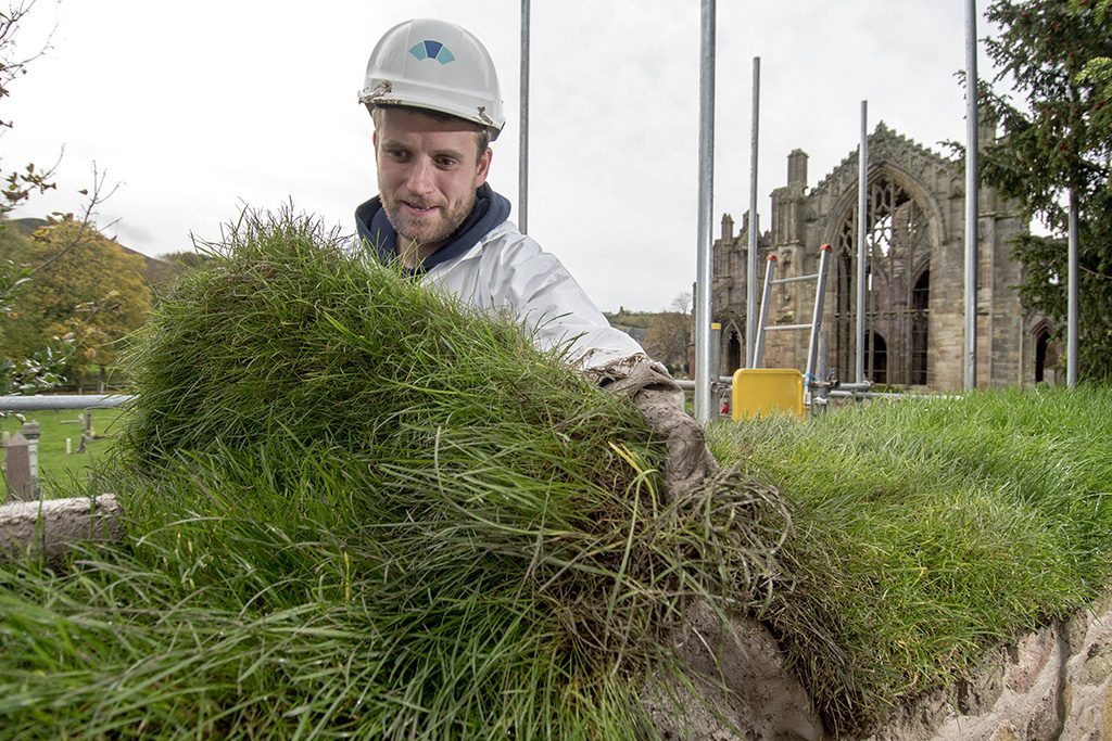 A stonemason covering the brewery yard wall at Melrose Abbey with turf