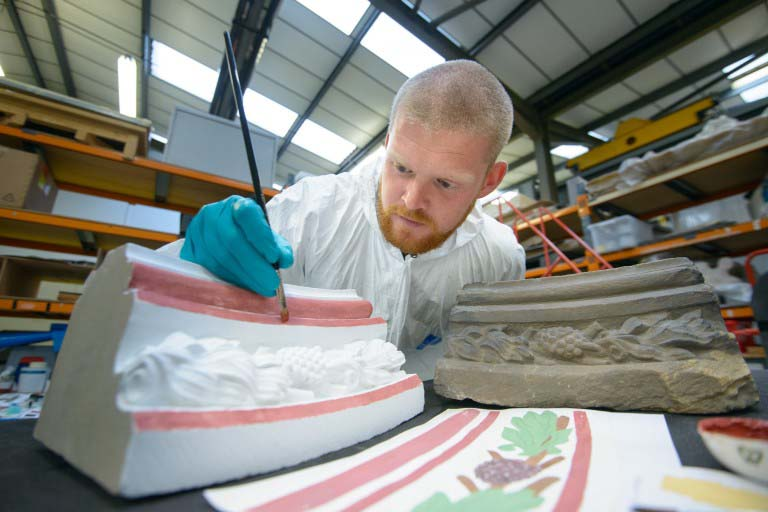 A man paints a carved replica of a stone using red paint