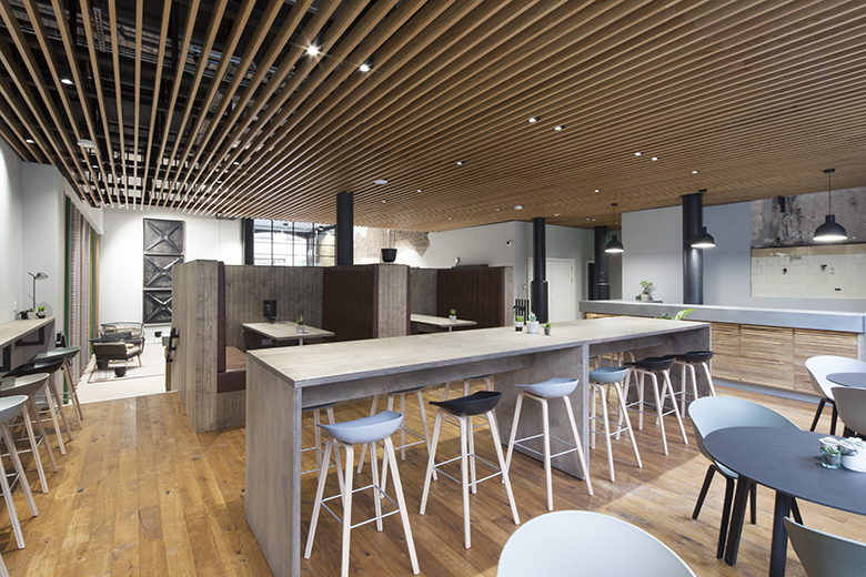 The inside of The Garment Factory in Glasgow featuring a high table with modern chairs in the centre