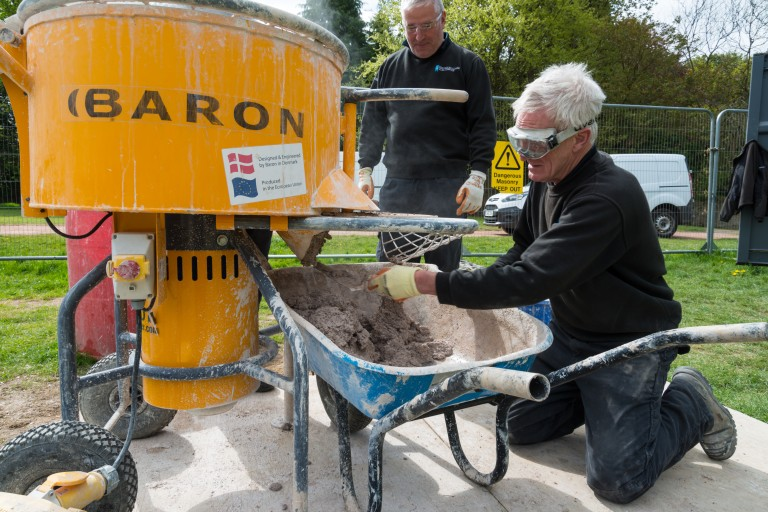 A man prepares hot lime mortar in a wheelbarrow