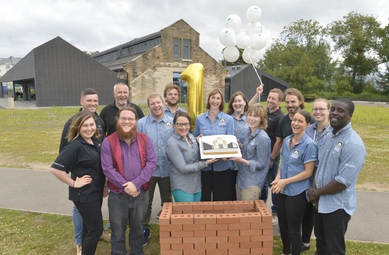 Staff stand outside the Engine Shed holding a big birthday cake and ballons