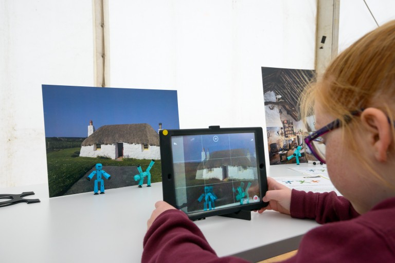 A child recording an animation using stick figurines and a photo of a traditional building