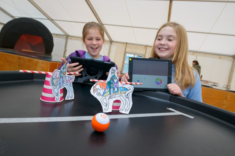 Two children use sphero robots and drawings of people jousting on a table