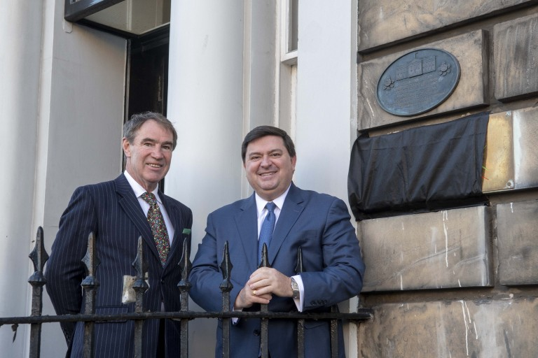 Two people stand smiling outside a new plaque on a traditional building
