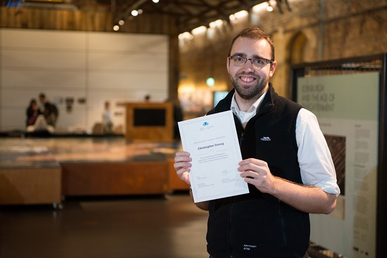 Chris standing inside the Engine Shed main space, smiling, and holding up a certificate