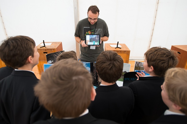 Chris showing schoolchildren an ipad and photos of traditional buildings