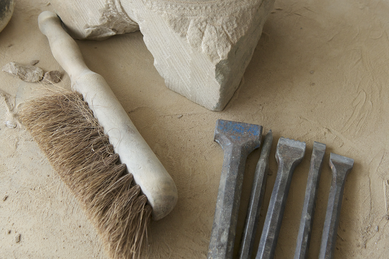 A brush, chisels and stone on top of a table