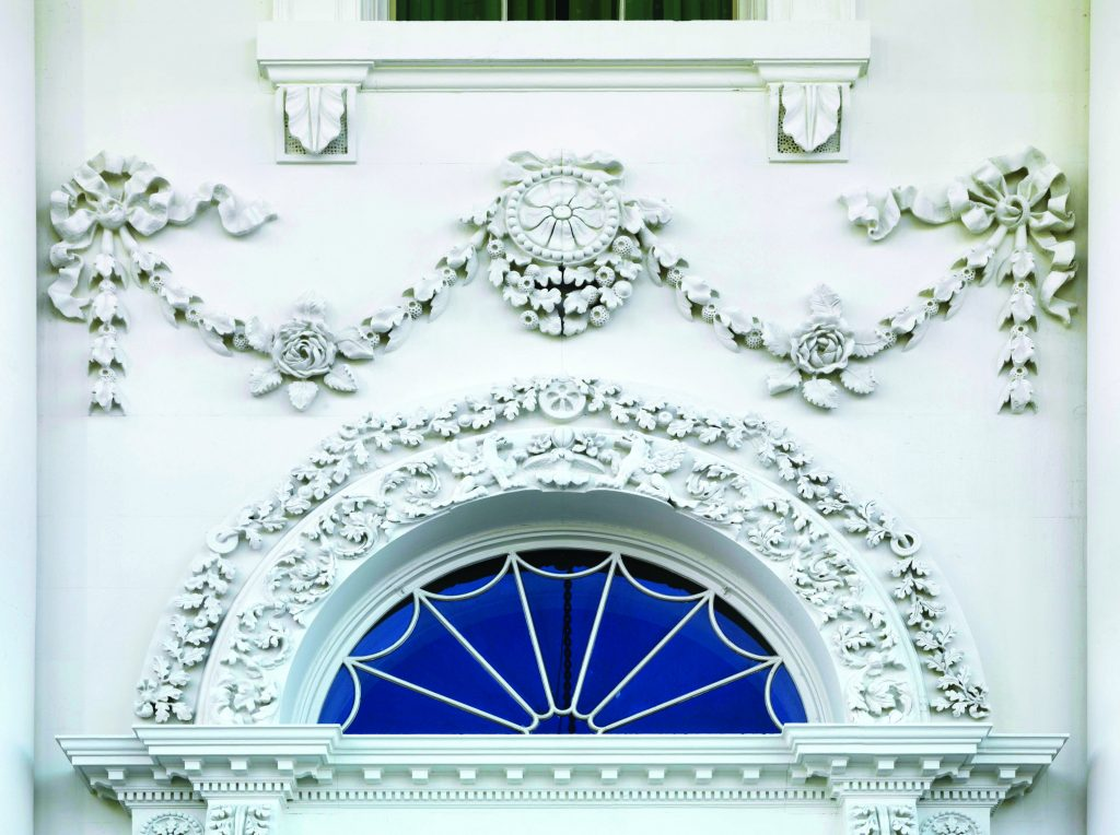 Detailed stone carvings above a door on the White House featuring a garland and flowers