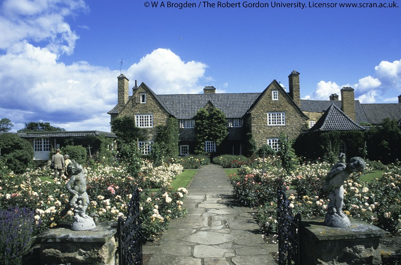The exterior with a wide pathway leading to the house flanked by two symmetrical gardens with yellow and pink flowers. Two small statues and gates lead into the path.