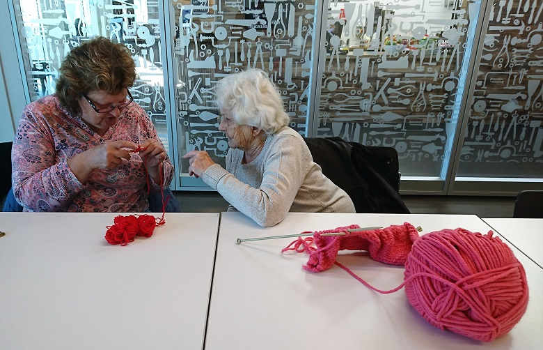 Two people knitting inside the Engine Shed using pink wool