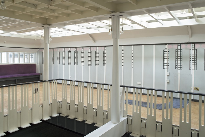 A gallery, with columns and balustrades. The room also has a purple sofa in it.