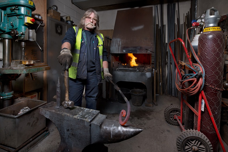 A blacksmith standing beside an anvil, holding a hammer and piece of hot metal