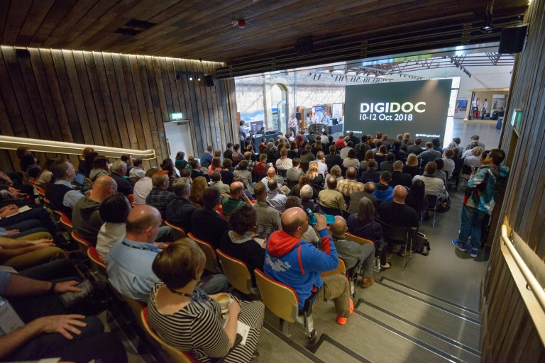People sitting inside the Engine Shed auditorium with a DigiDoc slide on a screen