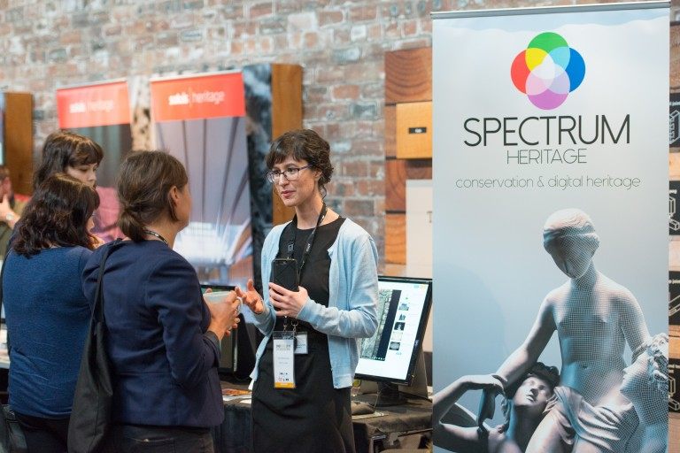 People talking inside the Engine Shed beside a Spectrum Heritage banner