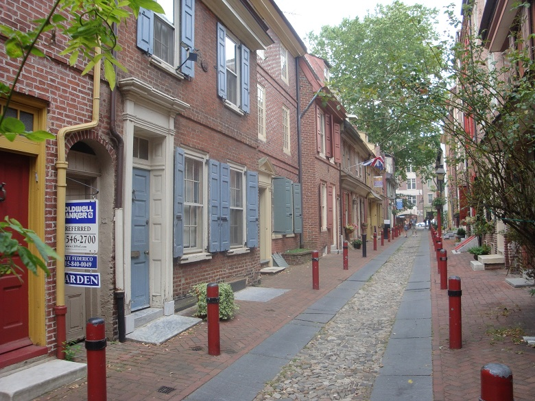 An alley with historic brick buildings with blue shutters
