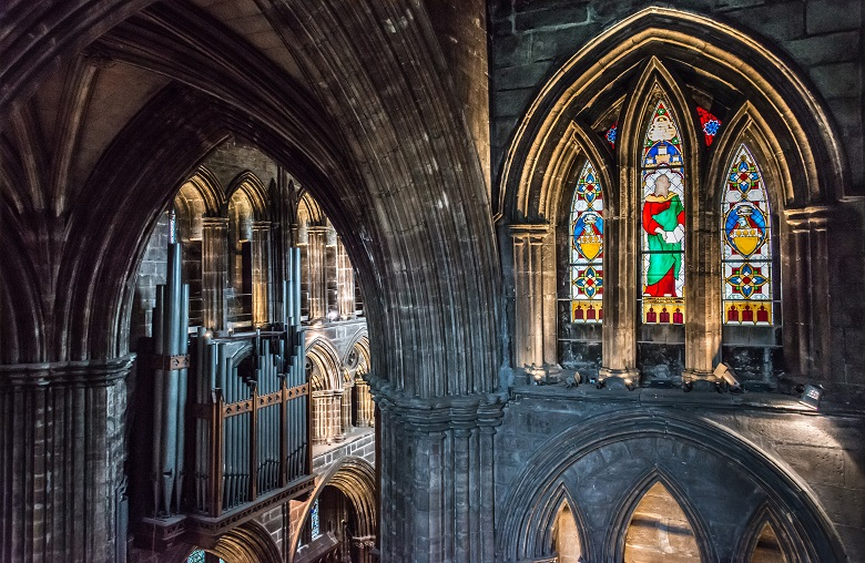 A look inside Glasgow Cathedral featuring a stained glass window and organ
