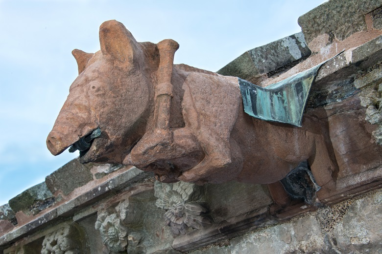 A stone carving of a pig playing the bag pipe