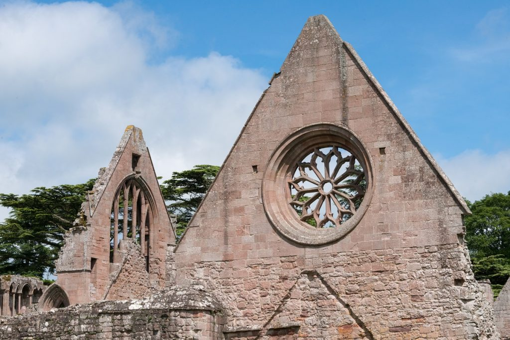 A circular window with a floral design at Dryburgh Abbey