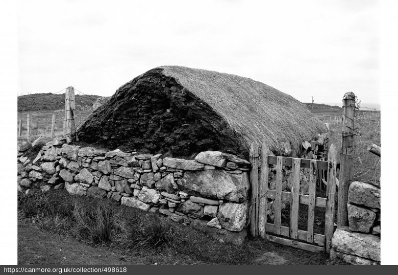 A black and white photo of an old building, with a stone wall and little wooden fence surrounding it