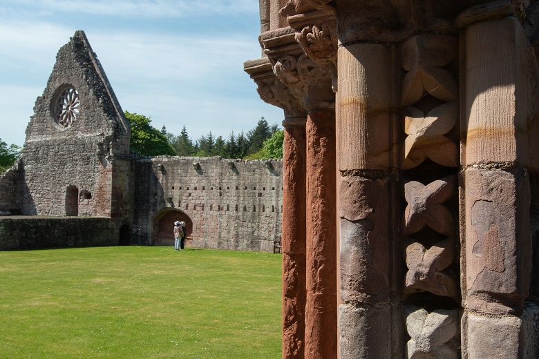 Stonework at Dryburgh Abbey, with part of the Abbey walls in the background