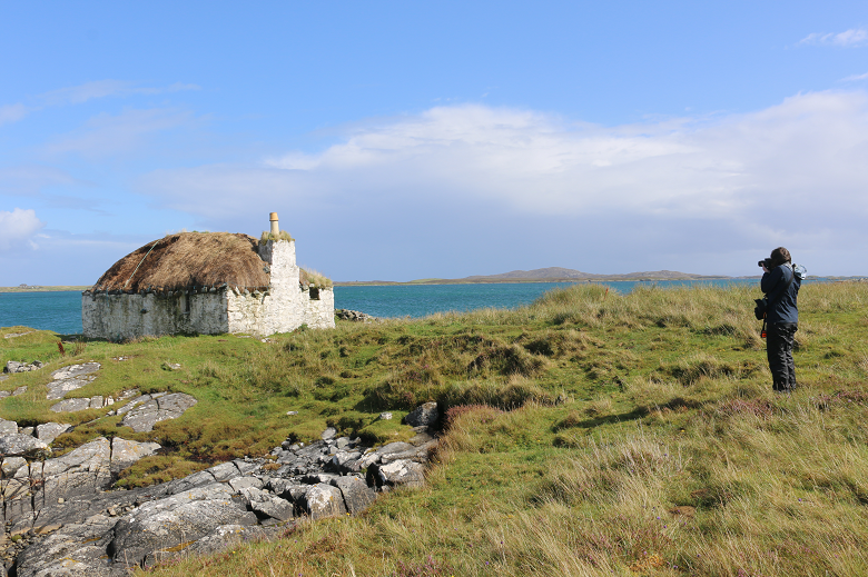 A thatched building, surrounded by grassland, overlooking the sea