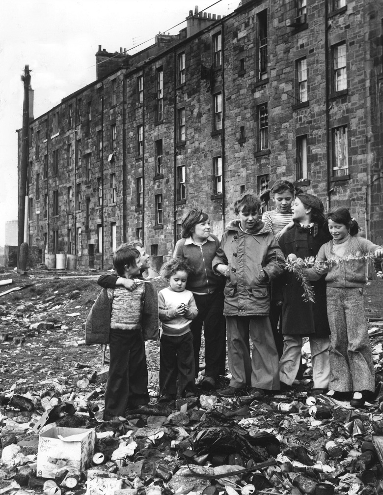 Children standing outside a block of tenement flats in a pile of rubbish