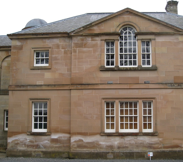 A large stone building with white marks from salt running along the bottom of the stone