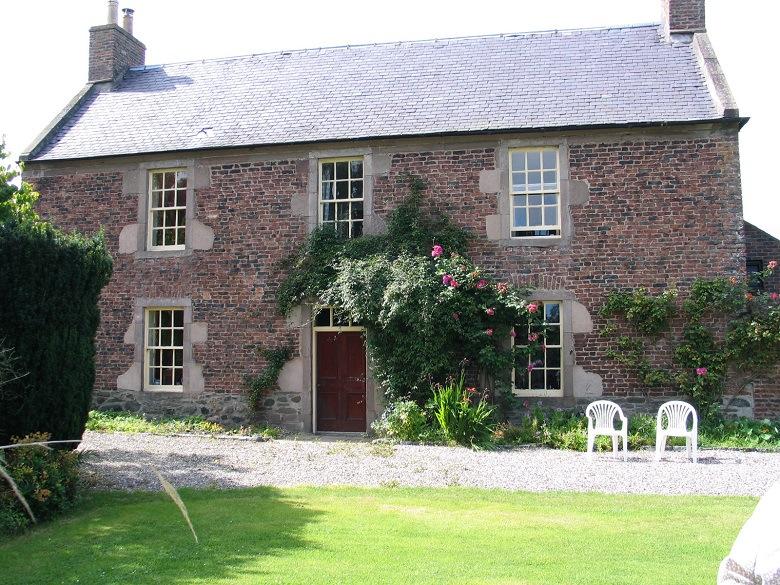 A large, brick house with six windows and two plastic chairs outside in the large garden