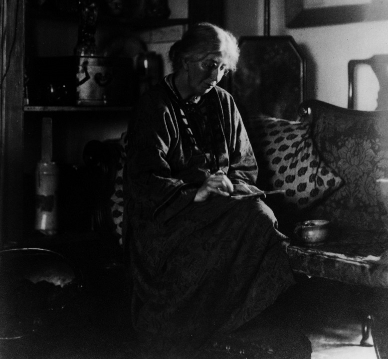 A black and white photo of a person embroidering while seated