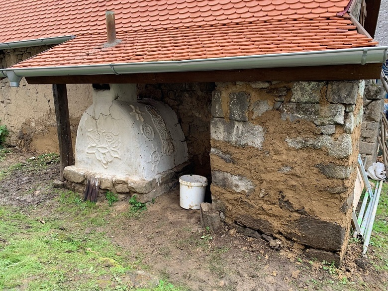 Part of a stone building with a red roof