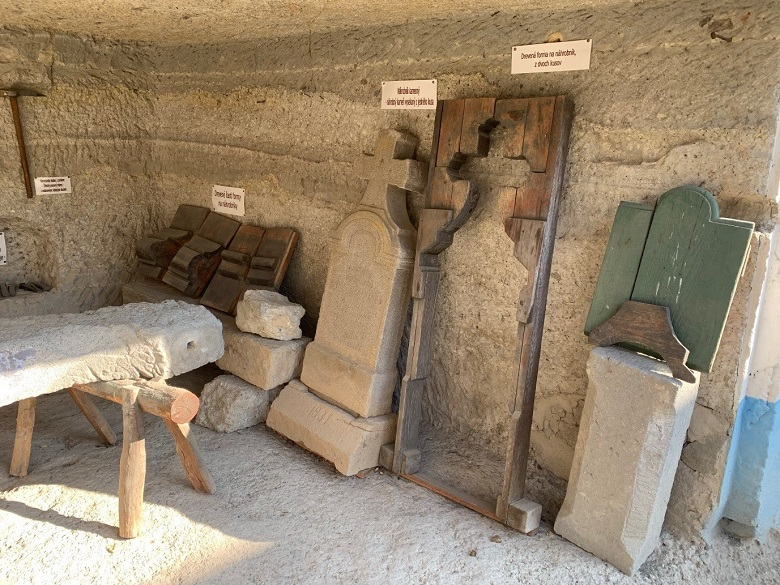 A workshop with gravestones, tools and a stone bench in it