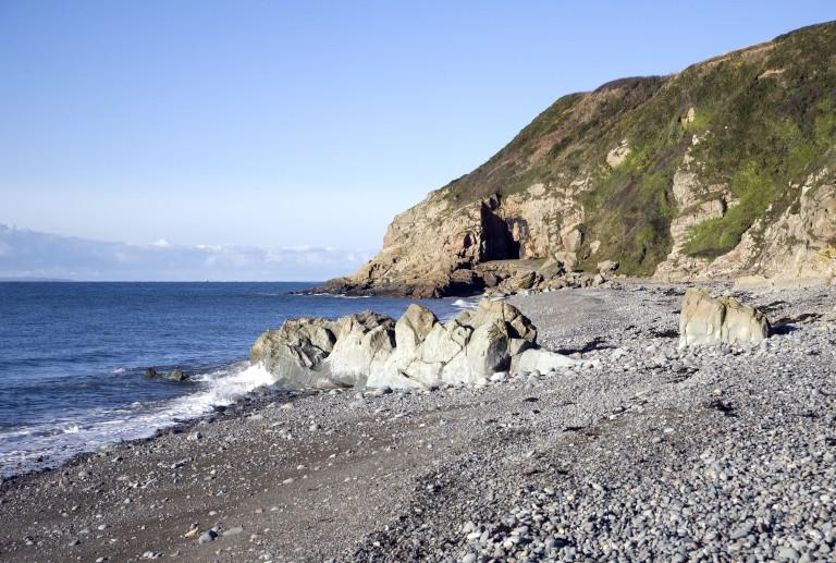 A cave on the coast with a stone beach