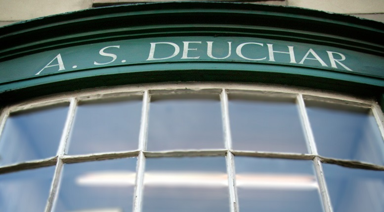 A curved shopfront window with the words A.S Deuchar above the window